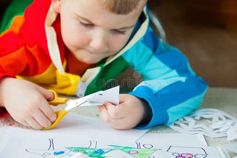 Um menino na roupa colorida brilhante cinzela flocos de neve do ano novo fotografia de stock royalty free
