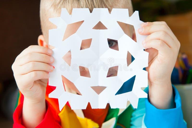 Um menino na roupa colorida brilhante cinzela flocos de neve do ano novo imagens de stock