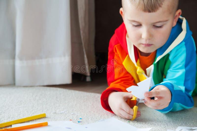 Um menino na roupa colorida brilhante cinzela flocos de neve do ano novo imagem de stock