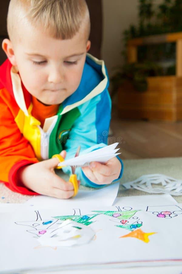 Um menino na roupa colorida brilhante cinzela flocos de neve do ano novo fotos de stock