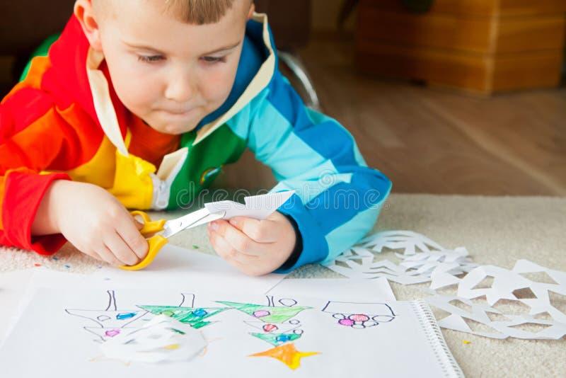 Um menino na roupa colorida brilhante cinzela flocos de neve do ano novo imagem de stock royalty free