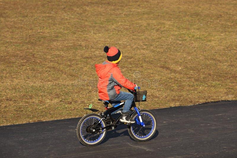 Um menino na roupa da demi-estação monta uma bicicleta em uma estrada asfaltada A geração mais nova é contratada nos esportes e g imagens de stock royalty free