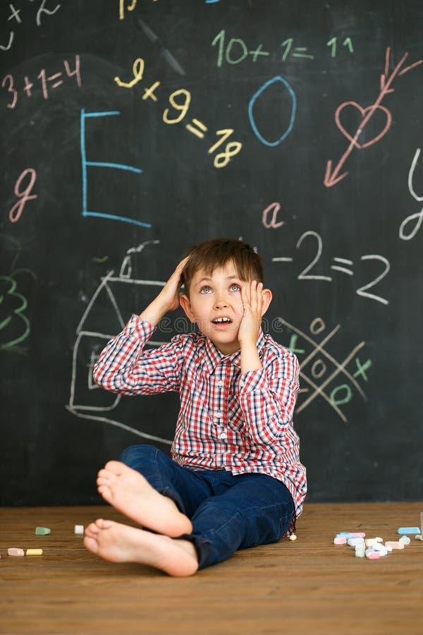 Um menino no fundo de um quadro-negro resolve uma tarefa dificil Senta-se com pastéis e risca-se sua cabeça fotos de stock