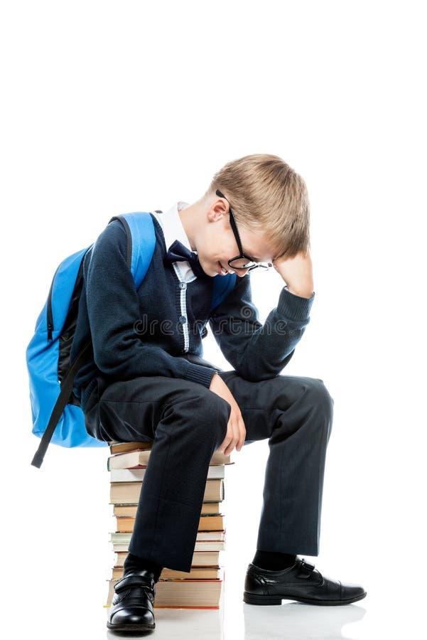 Um menino no pensamento senta-se em uma pilha dos livros em um branco fotos de stock