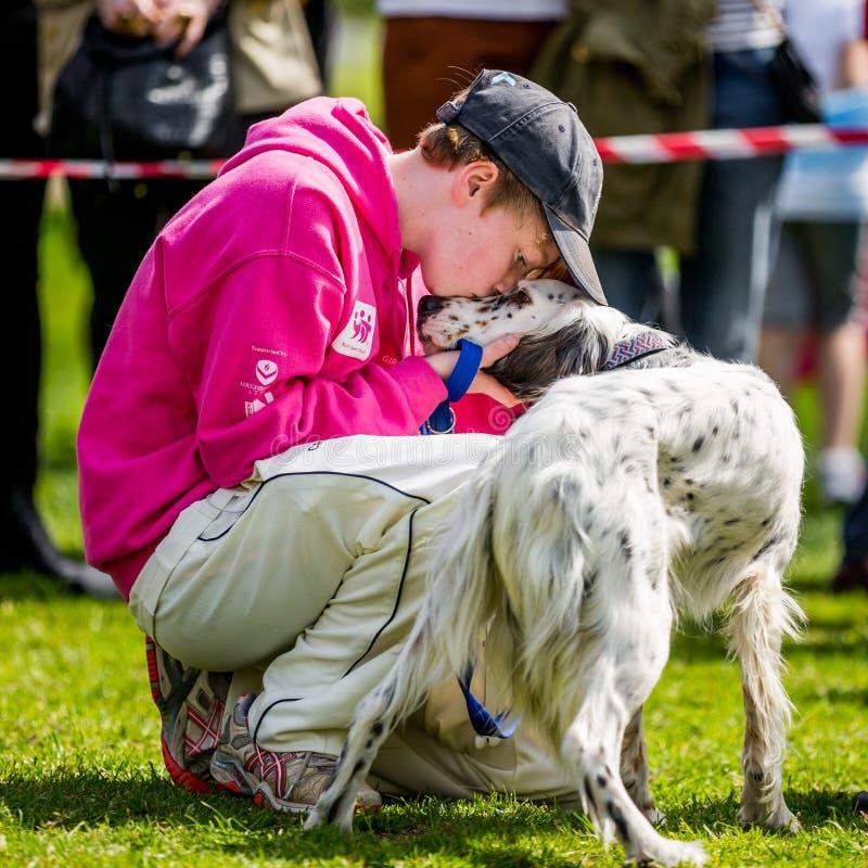 Um menino novo com um cão que beija seu nariz de cães na exposição de cães de Hampstead Heath fotos de stock royalty free