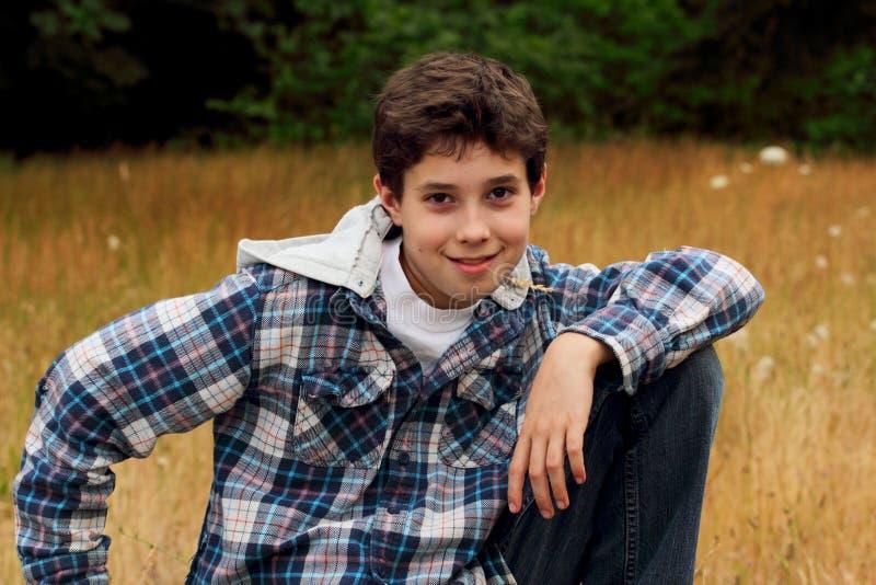 Um menino novo do Preteen que mastiga na grama fotografia de stock