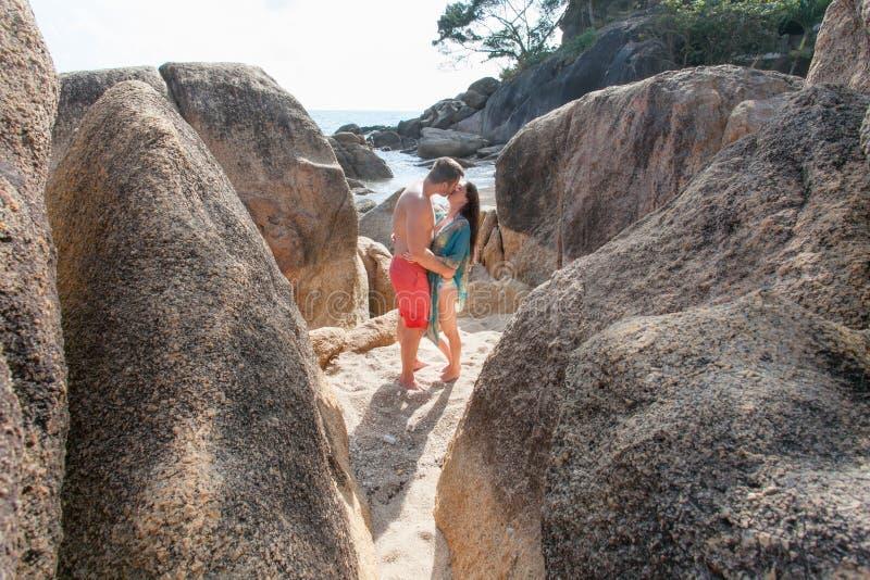 Um menino novo e uma morena de cabelos compridos da menina que beijam entre as grandes pedras na praia imagem de stock royalty free