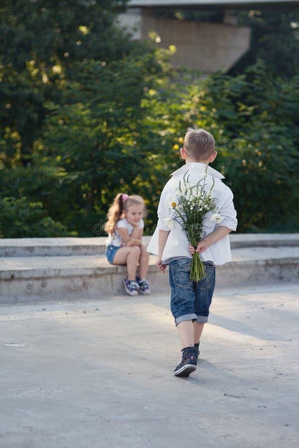 Um menino novo está aproximando-se à menina com flores foto de stock royalty free