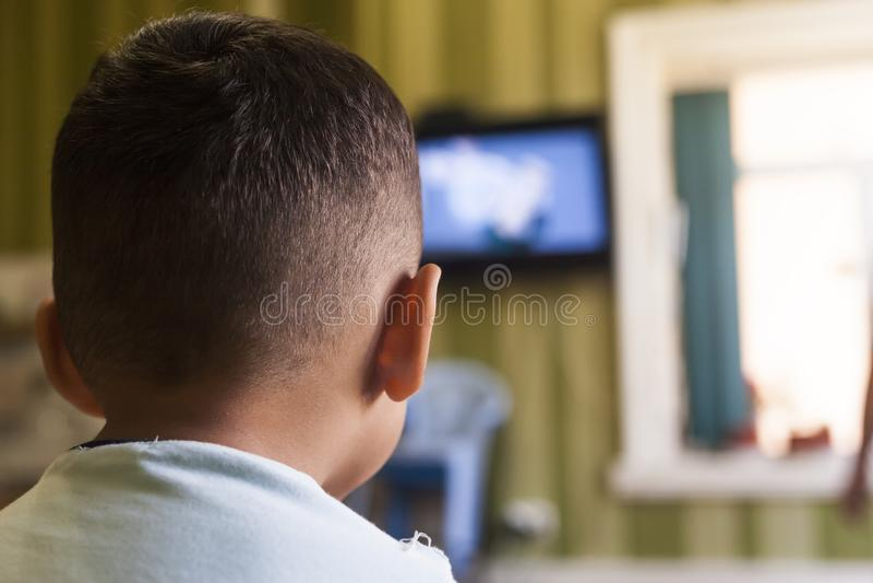 Um menino novo está olhando uma tela da televisão com seu para trás para um efeito da tevê em crianças ou em um conceito de uma c foto de stock