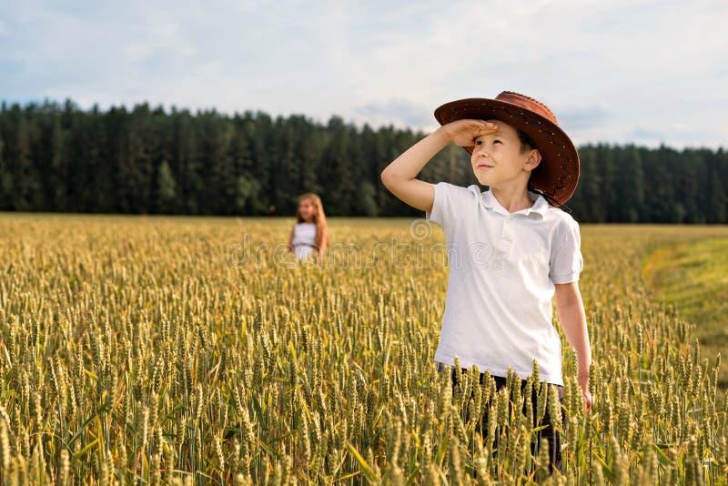 Um menino olha acima ao céu no campo de trigo em um chapéu de vaqueiro e em uma menina em um fundo distante imagens de stock