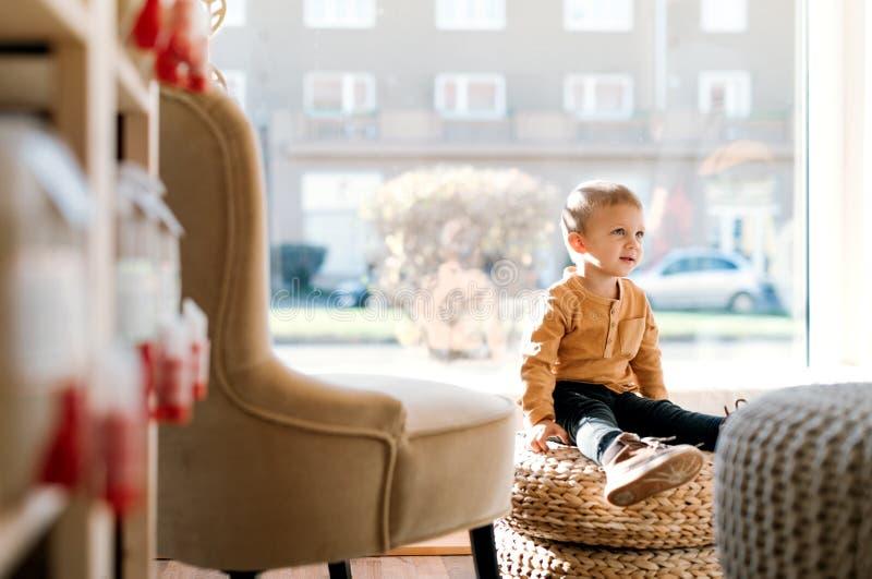 Um menino pequeno da criança que senta-se na loja zero do desperdício Copie o espaço fotos de stock