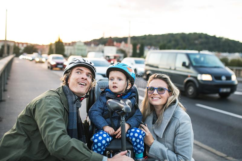 Um menino pequeno da criança que senta-se no assento de bicicleta com pais novos fora na cidade imagem de stock royalty free