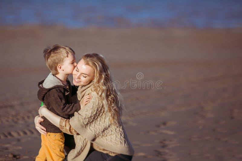 Um menino pequeno está beijando seu mum fotografia de stock