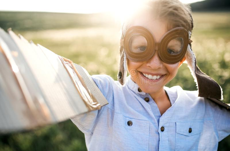 Um menino pequeno que joga em um prado na natureza, com óculos de proteção e asas como se voando imagens de stock royalty free