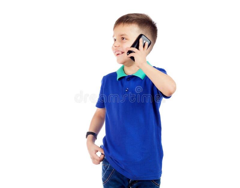 Um menino pré-escolar em um t-shirt azul está falando no telefone e na manutenção programada imagem de stock