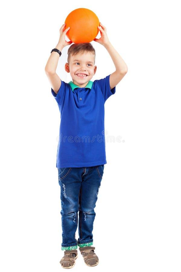 Um menino pré-escolar em um t-shirt azul está guardando a bola sobre seu h fotografia de stock royalty free