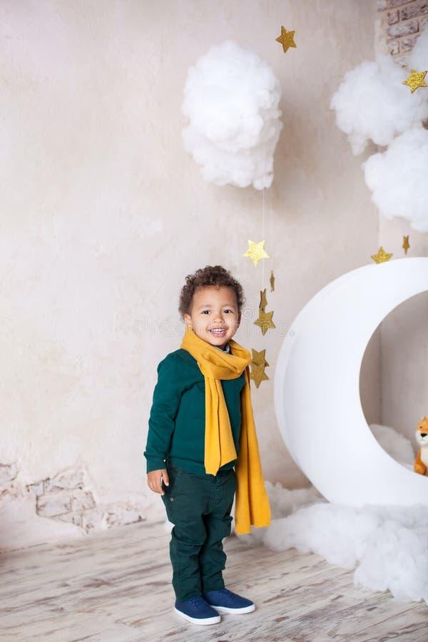 Um menino preto está perto do mês, nluna, entre as estrelas Uma criança no jogo, na fantasia Aventuras do príncipe pequeno Afric imagem de stock royalty free