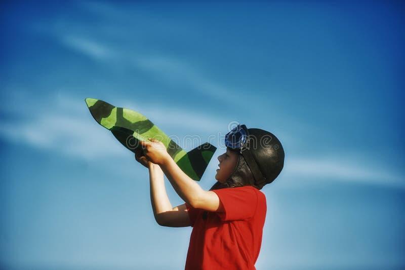 Um menino que joga com um modelo de madeira do plano imagem de stock