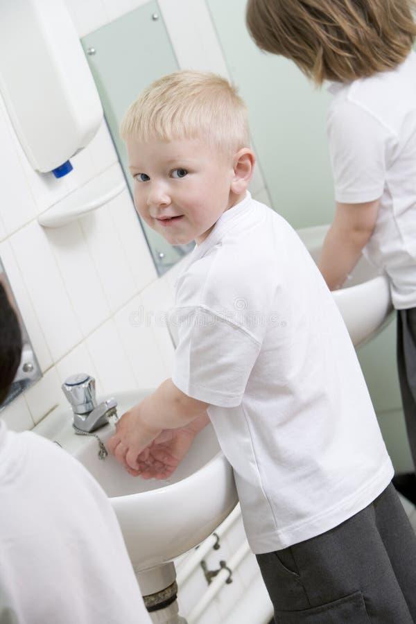 Um menino que lava suas mãos em um banheiro da escola foto de stock