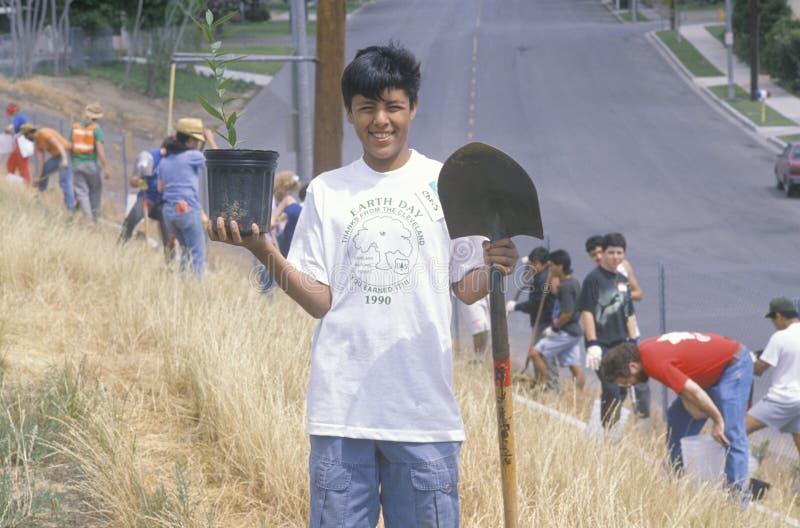 Um menino que veste um t-shirt do Dia da Terra que participa em uma plantação de árvores pelos voluntários limpos & verdes da Los fotos de stock royalty free