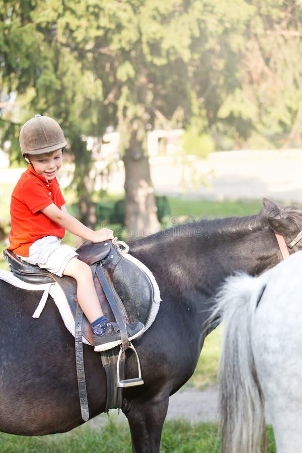 Um menino que vestem a camisa alaranjada e um capacete que senta-se sobre um cavalo fotografia de stock