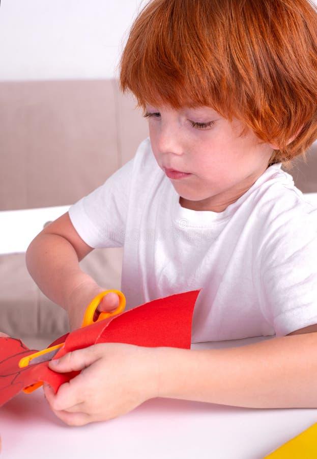 Um menino ruivo pequeno senta-se na tabela e corta-se do papel colorido com tesouras Está aprendendo e está tornando-se imagem de stock royalty free