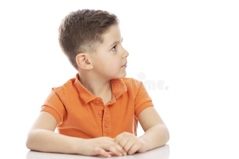 Um menino sério da idade escolar em um t-shirt alaranjado brilhante do polo senta-se em uma tabela e em olhares ao lado Close-up  fotografia de stock