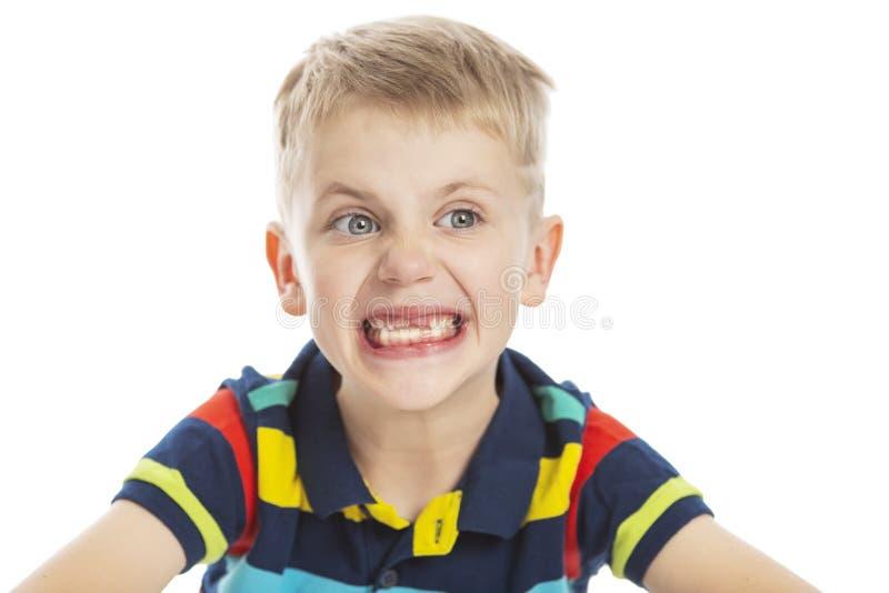 Um menino sem sorrisos dos dentes anteriors amplamente Isolado em um fundo branco imagem de stock royalty free
