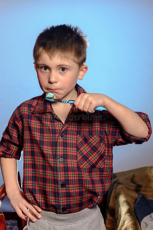 Um menino triste nos pijamas não é afiado escovar seus dentes antes de ir dormir em um fundo azul foto de stock royalty free