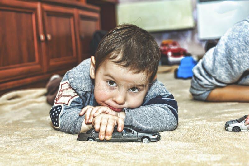 Um menino triste pequeno com um olhar pensativo Rapaz pequeno que joga carros do brinquedo em casa no tapete fotografia de stock