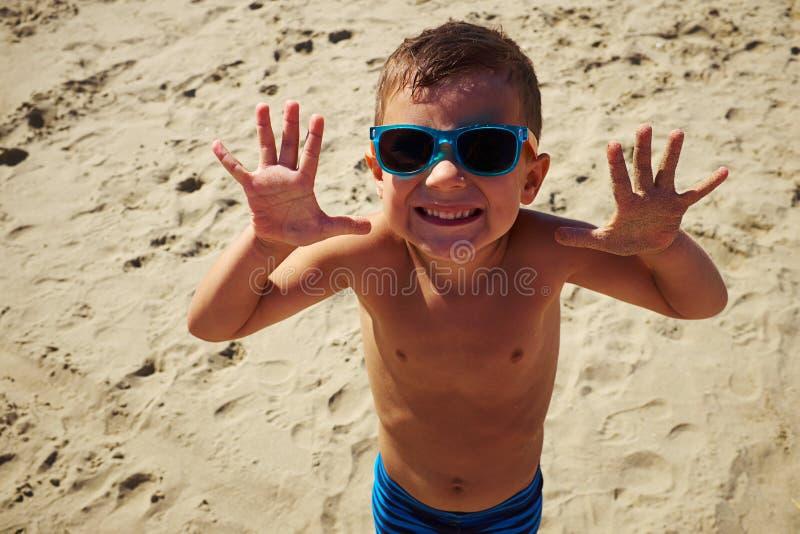 Um menino vívido nos óculos de sol que sorri na câmera na praia foto de stock royalty free