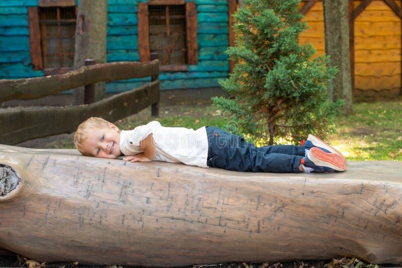 Um menino vestido em um t-shirt branco e em calças de brim está jogando no parque Estabelece em um banco feito de um tronco de ár foto de stock