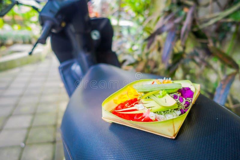 Um mercado com uma caixa feita das folhas, dentro de um arranjo das flores em um motorcyle, na cidade de Denpasar em Indonésia foto de stock royalty free