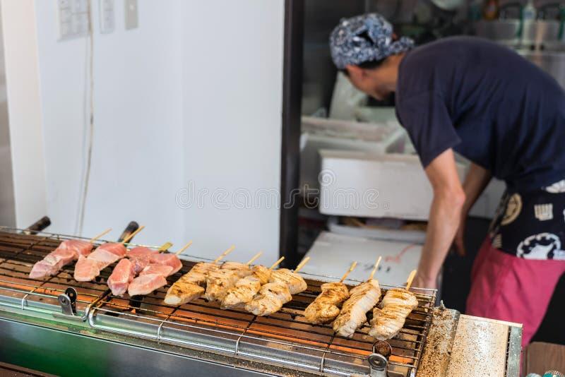 Um mercado de peixes de Is Cooking Tuna Sticks On A do cozinheiro imagem de stock
