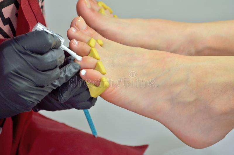 Um mestre do pedicure em um avental vermelho pinta as unhas do pé de uma menina com verniz para as unhas branco fotos de stock royalty free