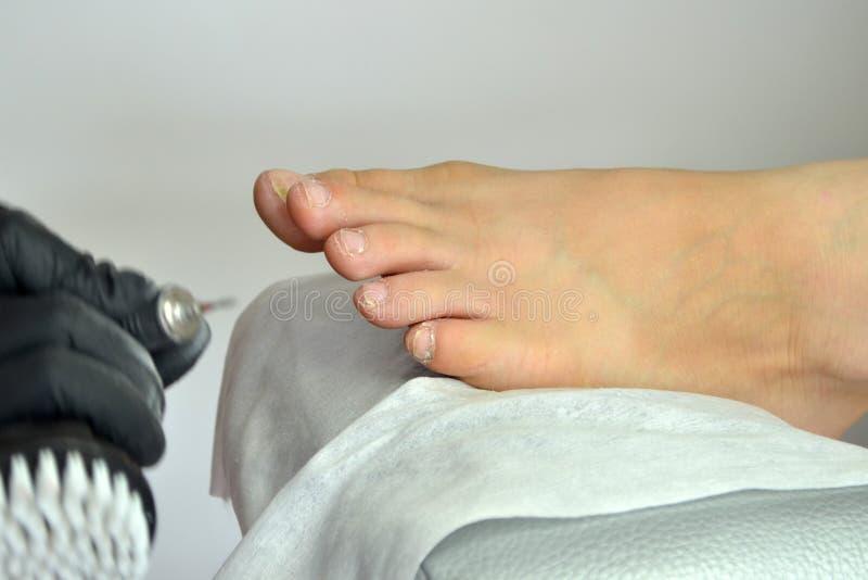 Um mestre do pedicure em luvas pretas está preparando-se para o trabalho com uma máquina de trituração do tratamento de mãos em p fotos de stock royalty free