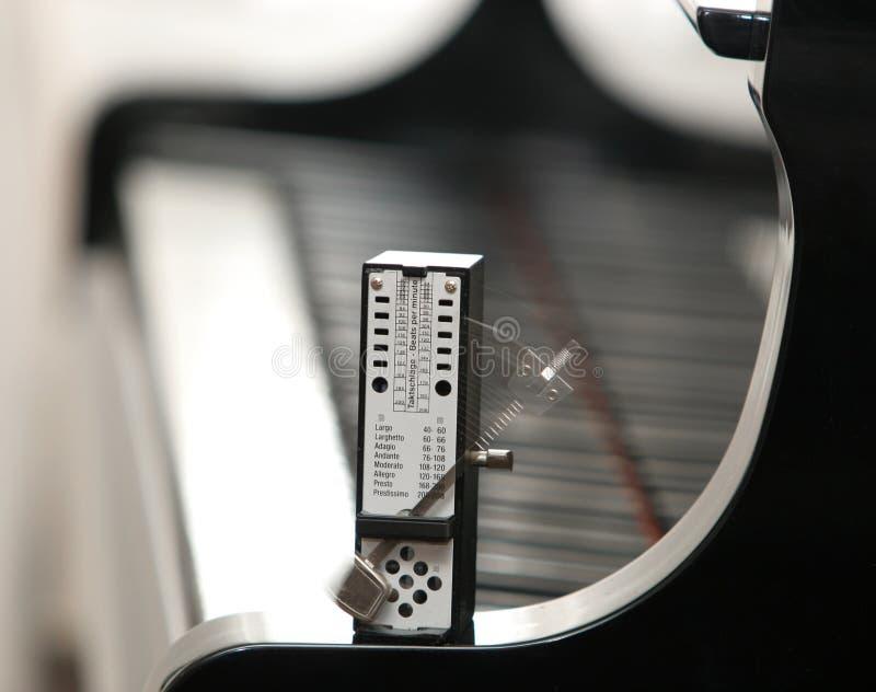 Um metrônomo em um piano imagens de stock royalty free