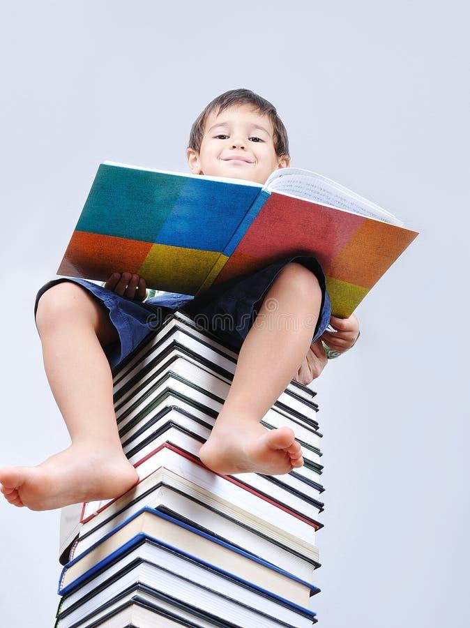 Um miúdo bonito pequeno e livros foto de stock