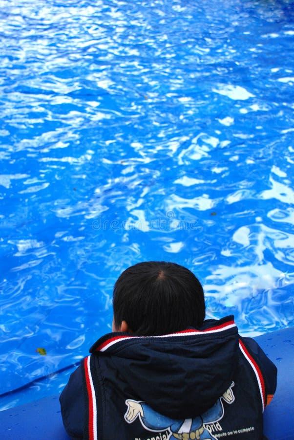 Um miúdo e uma água azul fotografia de stock