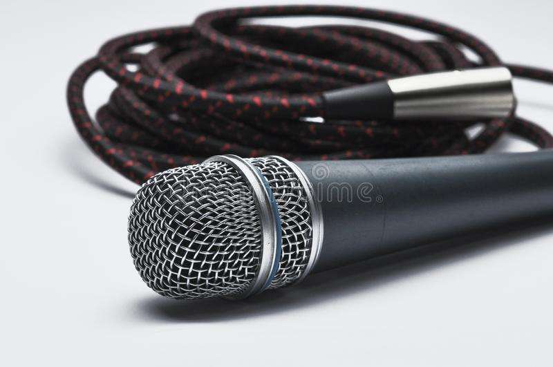 Um microfone com um cabo isolado em um fundo branco Copie o espa?o fotos de stock