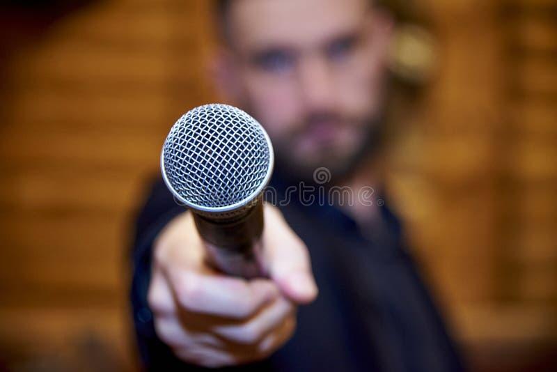 Um microfone na mão estendido de um homem farpado imagens de stock