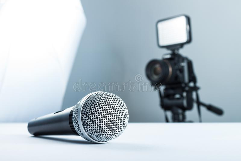 Um microfone sem fio que encontra-se em uma tabela branca na perspectiva da câmera de DSLR à luz conduzida foto de stock royalty free