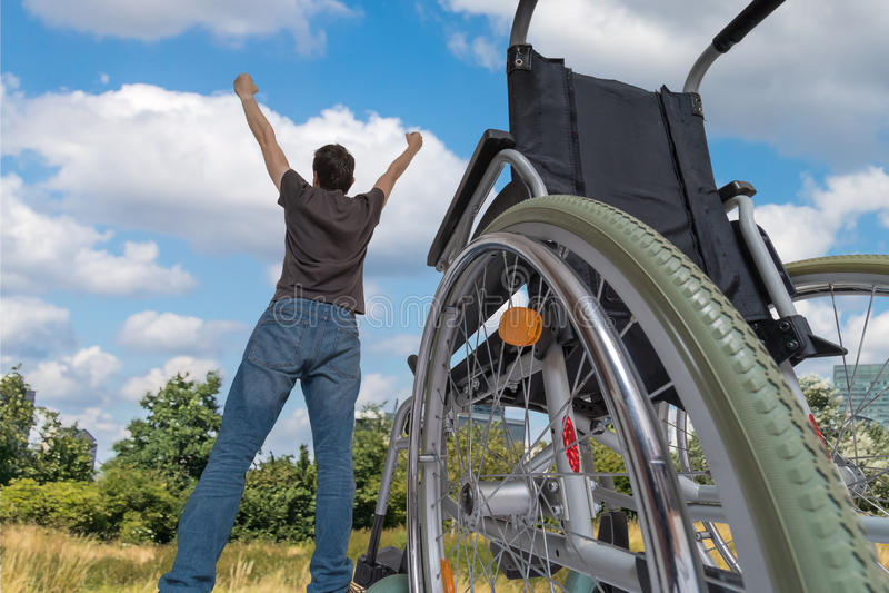 Um milagre aconteceu Desabilitou o homem deficiente é saudável outra vez É feliz e posição no prado perto de sua cadeira de rodas fotografia de stock royalty free