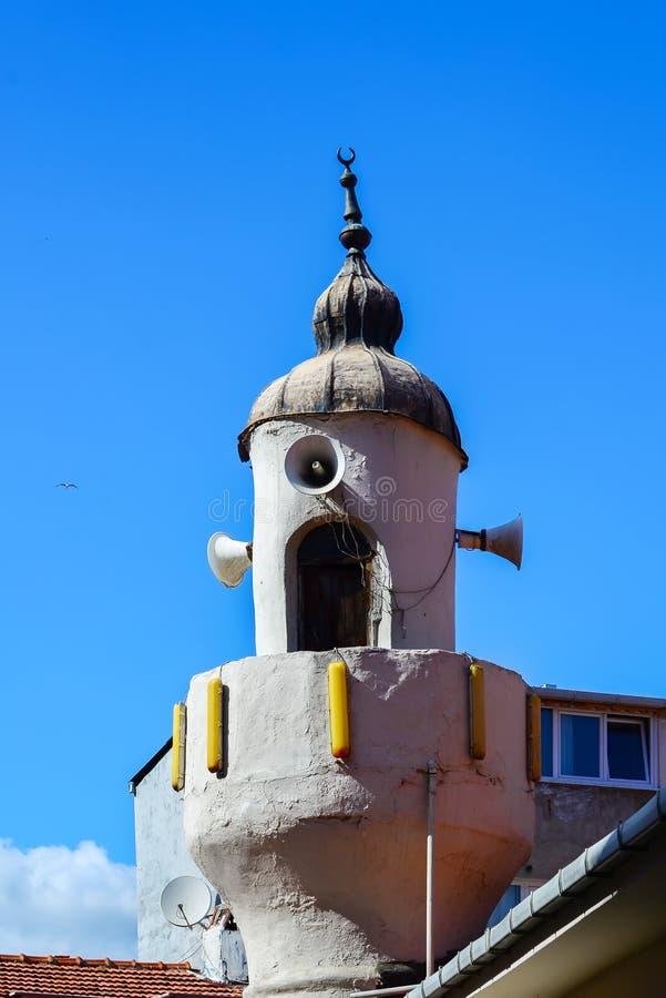 Um minarete velho de uma mesquita pequena contra o céu azul em Istambul imagem de stock