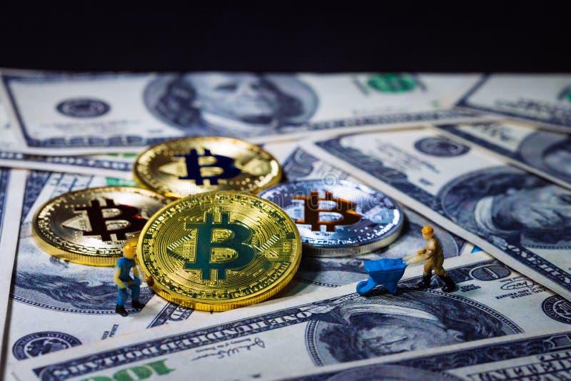 Um mineiro pequeno está escavando para a moeda digital do bitcoin dourado sobre cem fundos das cédulas do dólar Dinheiro da eletr imagem de stock royalty free