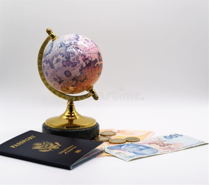 Um mini globo histórico, passaporte dos E.U. e lira turca que perderam em 2018 muito valor contra o dólar americano foto de stock