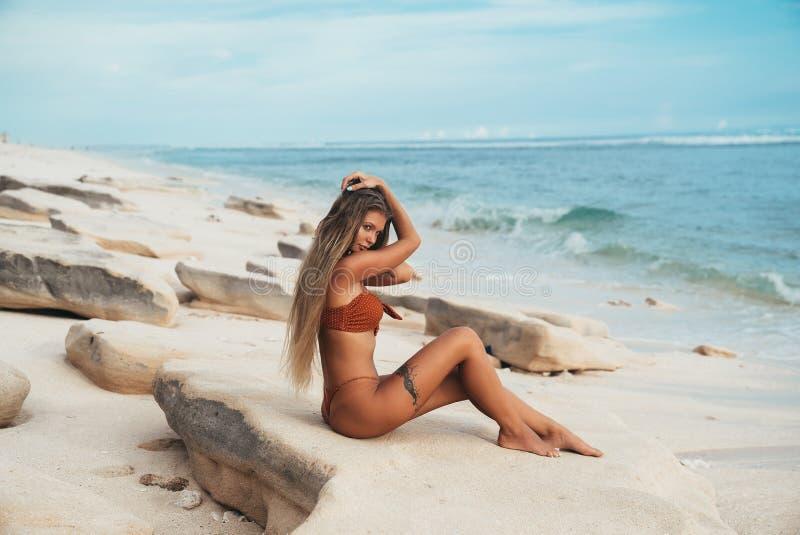 Um modelo com um montante suculento redondo e uns peitos luxúrias que levantam em uma pedra perto do mar A menina estava andando  fotos de stock royalty free