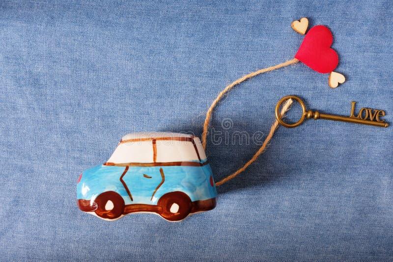 Um modelo do carro que reboca a chave da forma do amor e o mini coração vermelho, entregando o amor Valentine& feliz x27; conceit fotografia de stock