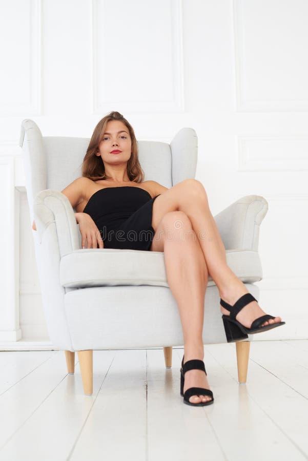 Um modelo fantástico com bordos vermelhos e em um vestido preto está sentando-se foto de stock