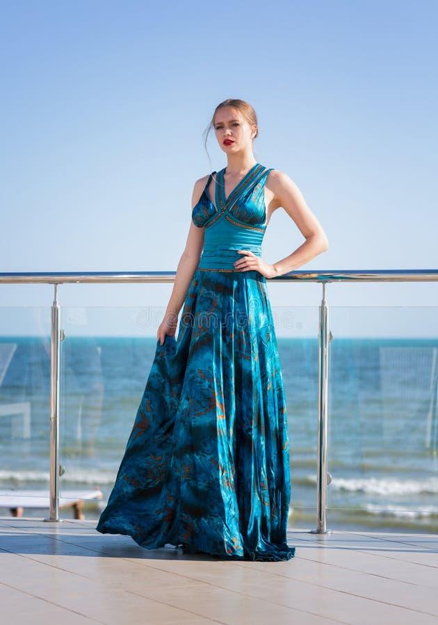 Um modelo novo atrativo e 'sexy' em um vestido longo está levantando em um fundo azul do mar Uma mulher encantador está levantand imagens de stock